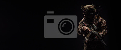 Naklejka Special forces United States soldier or private military contractor holding rifle. Image on a black background.