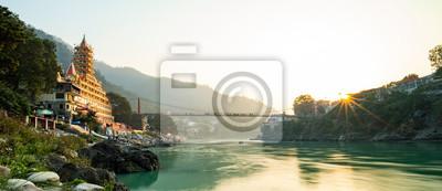 Naklejka Spektakularny widok świątyni Lakshman skąpanej przez świętą rzekę Ganges o zachodzie słońca.