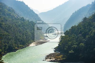 Naklejka Spektakularny widok świętej rzeki Ganges płynącej przez zielone góry Rishikesh, Uttarakhand, Indie.