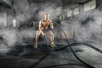 Naklejka Sportowy młody człowiek z batalistyczną arkaną robi ćwiczeniu w sprawności fizycznej gym. Pojęcie sportu.