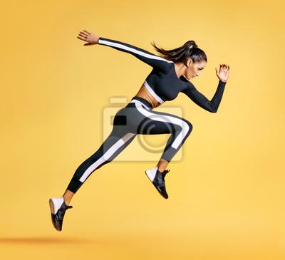 Naklejka Sporty kobieta biegacz w sylwetce na żółtym tle. Fotografia atrakcyjna kobieta w modnym sportswear. Dynamiczny ruch. Widok z boku. Sport i zdrowy styl życia