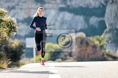 Naklejka Sporty young woman running on mountain road in beautiful nature.