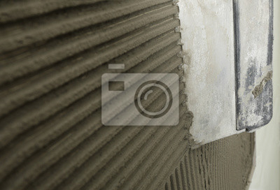 Spreading concrete on wall with spatula, closeup. Space for text