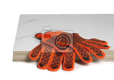 Stack of ceramic tiles and gloves on white background