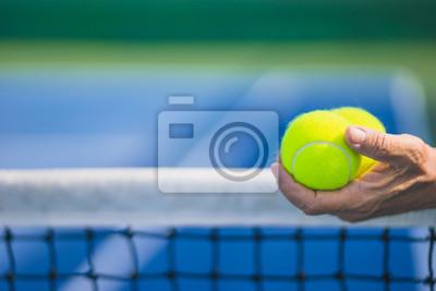 stary azjatycki człowiek trzymać dwie piłki tenisowe w lewej ręce, selektywne focus, niewyraźne netto i niebieski i zielony kort tenisowy jako tło, starzenie się pojęcie populacji