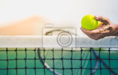 stary azjatycki człowiek trzymać dwie piłki tenisowe w lewej ręce, selektywne focus, niewyraźne rakieta, netto i zielony kort tenisowy jako tło, starzenie się pojęcie populacji