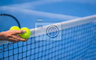 """stary azjatycki człowiek trzymać dwie piłki tenisowe w prawej ręce, selektywne focus, niewyraźne rakieta, netto i niebieski kort tenisowy jako tło, pojęcie """"starzenia się populacji"""""""