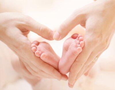 Stópki noworodka w rękach kochającej mamy ułożone na kształt serca