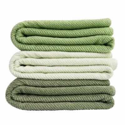Stos zielonych ręczników kąpielowych samodzielnie nad białym
