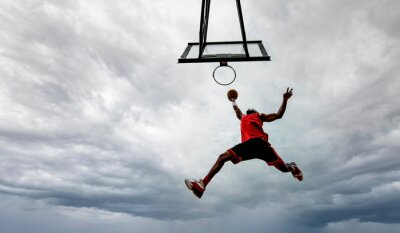 Naklejka Street basketball player making a powerful slam dunk on the court - Athletic male training outdoor on a cloudy sky background - Sport and competition concept