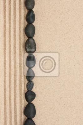 Stripe czarnych kamieni leżących na piasku