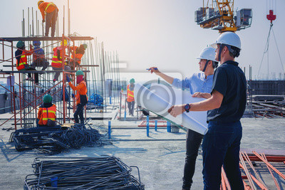 Naklejka Structural engineer and architect working with blueprints discuss at the outdoors construction site.