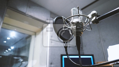 Naklejka Studio microphone or mic for recording for vocal singer or commercial announcer with shock mount and pop filter on professional tripod in acoustic foam room for best sound and mix process