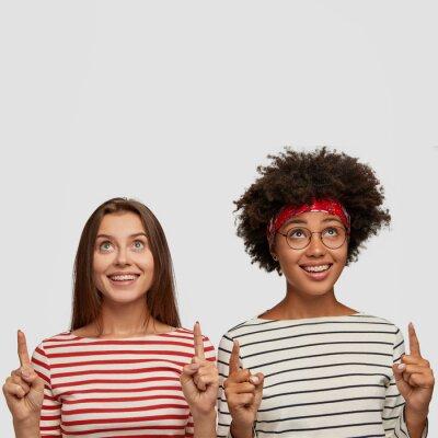 Naklejka Studio strzał zadowolonych kobiet z obu palców wskazujących, ciesz się wyrazami twarzy, patrz dziwne rzeczy, dyskutuj ze sobą, stań na białym tle, baw się dobrze w dobrym towarzystwie