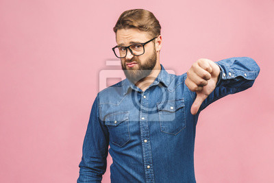 Naklejka Stylish fashionable male poses indoors against pink background, assess project, shows sign of dislike, looks with negative expression and disapproval. Disagreement, disgust and negative expressions