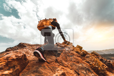 Naklejka Success woman hiker hiking on sunrise mountain peak - Young woman with backpack rise to the mountain top. Discovery Travel Destination Concept