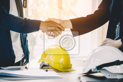 Naklejka Successful deal, male architect shaking hands with client in construction site after confirm blueprint for renovate building.