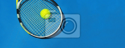Naklejka Summer sport concept with tennis ball and racket on blue hard tennis court. Flat lay, top view, copy space. Blue and yellow, banner size.