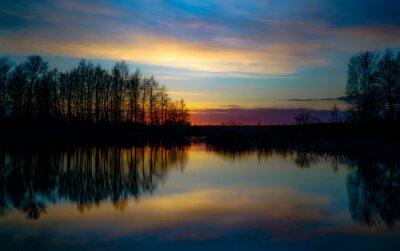 Naklejka sunset at coast of the lake. Sunset sky. Smooth water