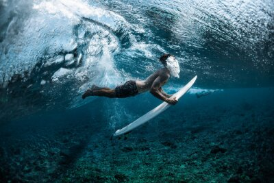 Naklejka Surfer performs dive (the duck dive) with his surfboard under the wave and exhales air into the water.