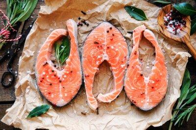 Naklejka Surowe steki z łososia z świeże zioła, sól i pieprz corns. Overhead view