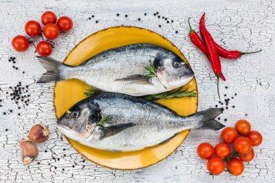 Naklejka Surowe świeże ryby dorado na żółty talerz i warzyw na białym stole. Widok z góry.
