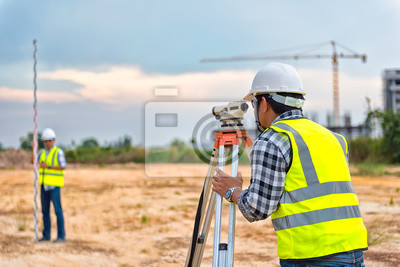 Naklejka Surveyor equipment. Surveyor's telescope at construction site or Surveying for making contour plans are a graphical representation of the lay of the land before startup construction work