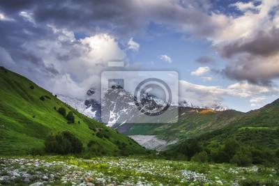 Svaneti górski krajobraz, Gruzja. Kaukaz dzikiej przyrody z ośnieżonymi górami skalistymi i trawiastymi wzgórzami. Zachmurzone niebo o zachodzie słońca nad szczytami montuje. Malownicze góry. Gruzińsk