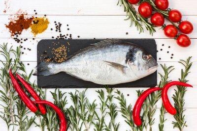Naklejka Świeże ryby dorado, rozmaryn, pomidory koktajlowe, chłodny pieprz na białym drewnianym stole. Widok z góry.