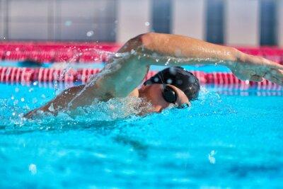 Naklejka Swimmer man doing crawl swim in swimming pool portrait. Closeup of athlete wearing goggles, swimming cap training in blue water indoors.