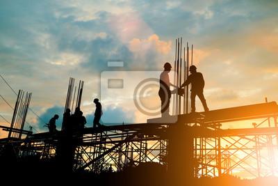 Naklejka Sylwetka inżyniera i budowy drużynowy działanie przy miejscem nad zamazanym tło zmierzchu pastelem dla przemysłu tła z Lekkim jarmarkiem.