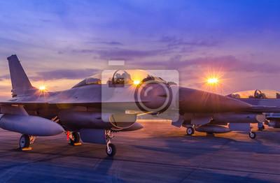 Naklejka Sylwetka myśliwca wojskowego samolotu zaparkowanego na pasie startowym w czasie zmierzchu z lekkim lotniskiem podczas pokazu lotniczego w nocy