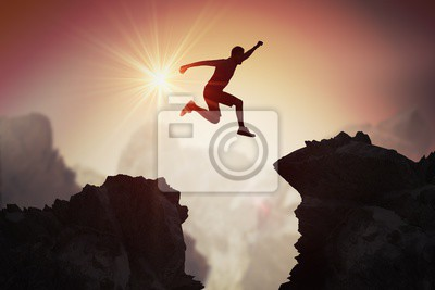 Naklejka Sylwetka skacze nad górami i falezami przy zmierzchem młody człowiek.