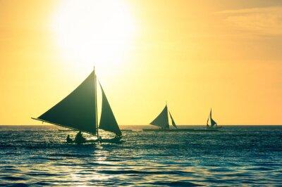 Naklejka Sylwetka typowych łodzi żaglowych o zachodzie słońca w wyspie Boracay w Filipiny