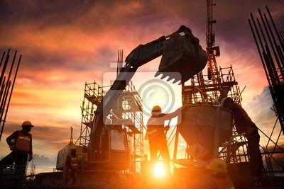 Naklejka Sylwetka zespoły inżynierów biznesowych poszukuje projektów w budowie przez niewyraźne budowy o zachodzie słońca.