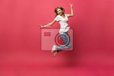 Naklejka szczęście, wolność, ruch i ludzie pojęć, - uśmiechnięta młoda kobieta skacze w powietrzu nad różowym tłem