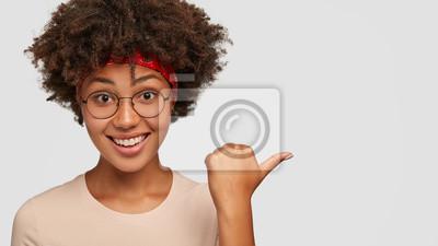 Naklejka Szczęśliwa czarna etniczna kobieta uśmiecha się radośnie, pokazuje kciukiem na bok, pokazuje sklep, w którym kupiła nowy strój, nosi okulary, jest czymś zaskoczona, modelki na białej pustej ścianie st
