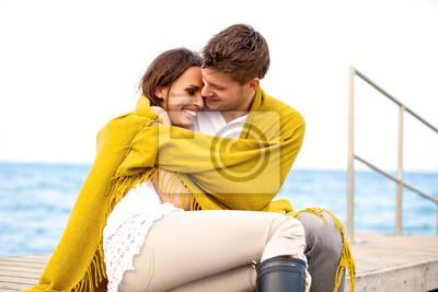 Szczęśliwa młoda para siedzi razem na molo