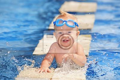 Szczęśliwe dziecko bawi się z bryzgami wody w basenie