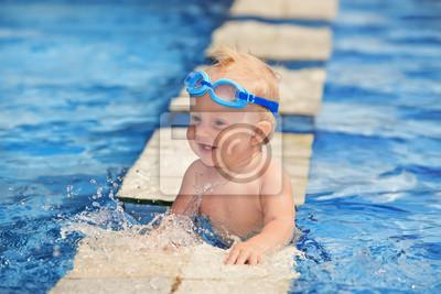 Szczęśliwe dziecko bawi się z bryzgami wody w basenie przed