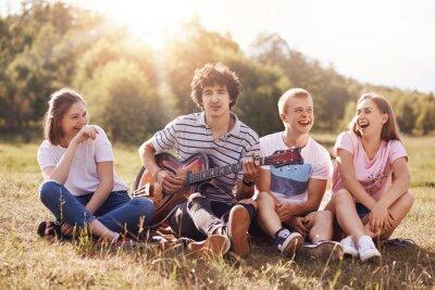 Naklejka Szczęśliwe kobiety i mężczyźni studiują na pikniku na świeżym powietrzu, siadają razem, śmieją się i żartują, śpiewają piosenki na gitarze, podziwiają piękną naturę. Ludzie, styl życia, koncepcja amuz