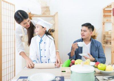 Szczęśliwi rodzinni kulinarni ciastka wpólnie w kuchni dla rodziny w domu