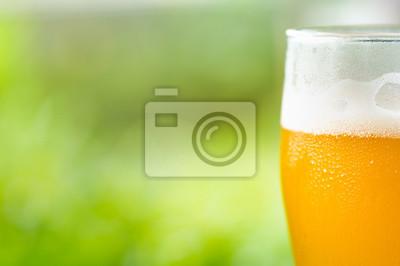 szklanka zimnego piwa rzemieślniczej z jasnym zielonym tle bokeh, selektywnym focus