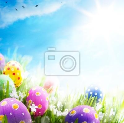 Sztuka pisanki ozdobione kwiatami w trawie na niebieskim niebie