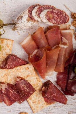 Naklejka Szynka, orzechy, krakersy i winogron na białym tle drewnianych