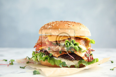 Naklejka Tasty burger with bacon on table against color background