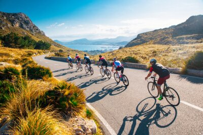 Naklejka Team sport cyclist photo. Group of triathlete on bicycle ride on the road at Mallorca, Majorca, Spain.