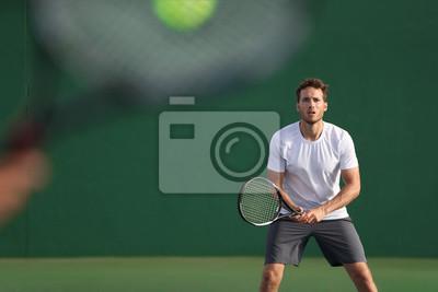 Naklejka Tenisista skupił się na uderzaniu piłką rakietą innego gracza na korcie. Mężczyźni sportowcy sportowcy grają razem w tenisa. Dwóch profesjonalnych tenisistów na twardym odkrytym boisku podczas gry.