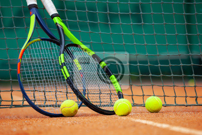 Naklejka Tennis rackets and balls leaned against the net.