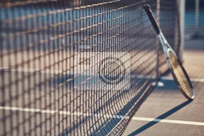 Naklejka Tennis racquet is standing near tennis net outside at bright sunny day.
